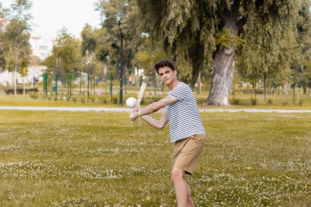 Photo pour Teenager boy holding softball bat and playing baseball in park - image libre de droit