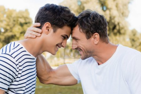 Photo for Side view of joyful father and teenager son looking at each other - Royalty Free Image