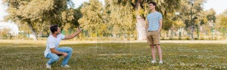 Photo pour Plan panoramique du père prenant des photos sur le fils joyeux debout avec les mains dans les poches dans le parc vert - image libre de droit