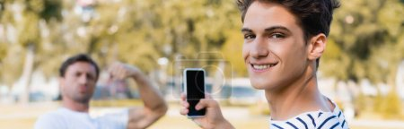 Photo for Horizontal concept of joyful teenager boy taking photo of father while holding smartphone in park - Royalty Free Image