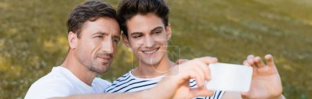 panoramic crop of father and teenager son taking selfie in park
