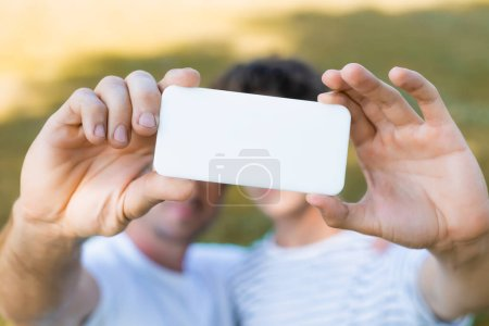 Photo pour Selective focus of smartphone in hands on father and teenager son taking selfie - image libre de droit
