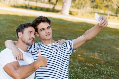 Photo pour Father showing thumb up and teenager son taking selfie in park - image libre de droit