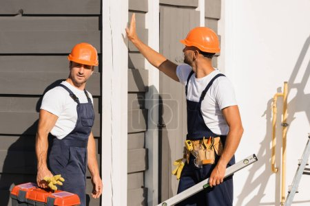 Photo for Builders in overalls holding toolbox and spirit level near building outdoors - Royalty Free Image