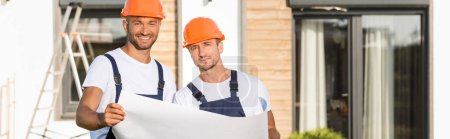 Photo for Horizontal crop of builders in hardhats holding blueprint outdoors - Royalty Free Image