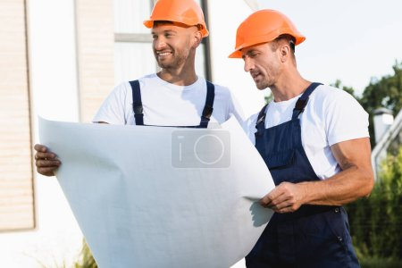 Builders in hardhats and uniform holding blueprint outdoors