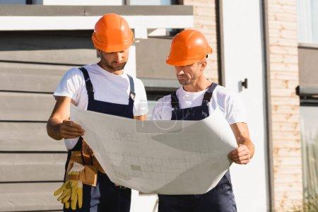 Photo pour Bâtisseurs tenant un plan directeur tout en travaillant près du bâtiment - image libre de droit