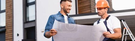 Photo for Horizontal concept of man holding blueprint near builder in uniform outdoors - Royalty Free Image