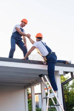 Photo pour Builder aide à collègue sur l'échelle près du toit du bâtiment - image libre de droit