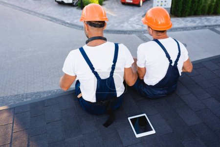 Back view of builders sitting near digital tablet on roof of building