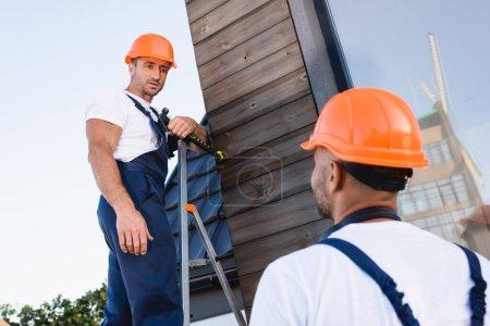 Selektiver Fokus des Bauarbeiters, der den Hammer hält, während er auf der Leiter in der Nähe des Kollegen und der Fassade des Gebäudes steht