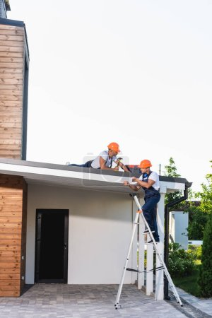 Builder on ladder holding digital tablet near colleague with hammer on roof of house