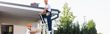 Photo for Horizontal crop of builders looking at camera while using ladder near building - Royalty Free Image