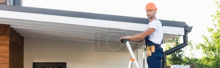 Photo for Panoramic shot of builder looking at camera while standing on ladder near roof of building - Royalty Free Image