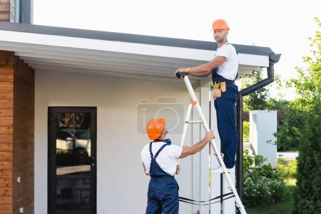 Photo for Handymen in hardhats and uniform using ladder near roof of building - Royalty Free Image
