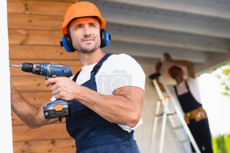 Photo for Selective focus of handyman in workwear and ear defenders holding electric screwdriver near facade of building - Royalty Free Image