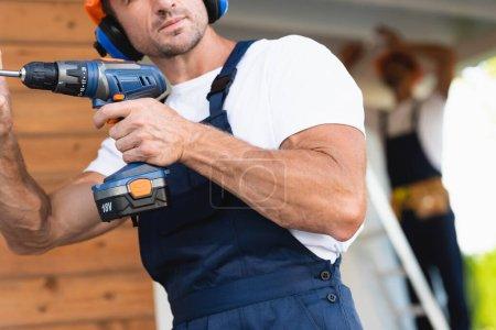 Photo pour Mise au point sélective du constructeur tenant un tournevis électrique près du bâtiment - image libre de droit