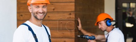 Photo pour Panoramic concept of builder looking at camera while colleague working with electric screwdriver near facade of building - image libre de droit