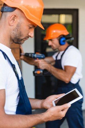 Foto de Enfoque selectivo del constructor que sostiene la tableta digital cerca del colega que trabaja cerca del edificio - Imagen libre de derechos