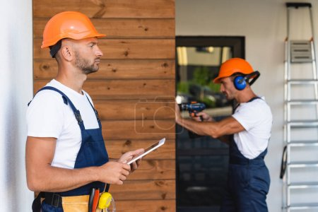 Photo pour Selective focus of builder in tool belt and workwear holding digital tablet near colleague and house - image libre de droit