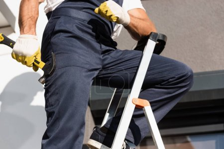 Photo pour Vue recadrée du marteau de maintien du constructeur debout sur l'échelle à l'extérieur - image libre de droit