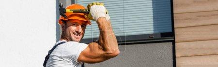 Photo pour Concept panoramique de constructeur en hardhat et gants tenant marteau près de la façade du bâtiment - image libre de droit