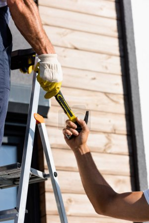 Photo for Cropped view of builders holding hammer near ladder and building - Royalty Free Image