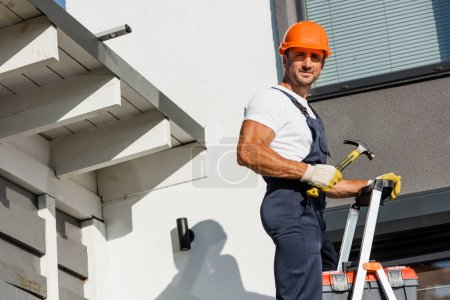 Builder in uniform and hardhat holding hammer near toolbox on ladder and facade of building
