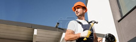 Photo pour Horizontal crop of builder holding hammer while standing on ladder near house - image libre de droit
