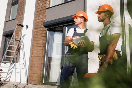 Photo pour Concentration sélective des travailleurs manuels avec boîte à outils en utilisant une tablette numérique près de la maison à l'extérieur - image libre de droit