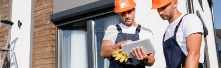 Photo pour Image horizontale des ouvriers en hardhats et uniforme à l'aide d'une tablette numérique près de la maison - image libre de droit
