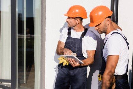 Foto de Constructores en cascos usando tableta digital al lado de la construcción al aire libre - Imagen libre de derechos
