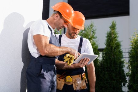 Photo pour Handyman in overalls using digital tablet while standing near facade of house - image libre de droit