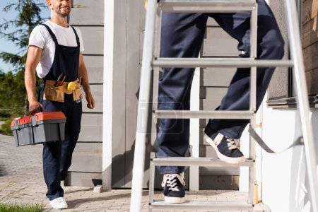 Photo for Selective focus of builder holding toolbox near colleague on ladder near house - Royalty Free Image
