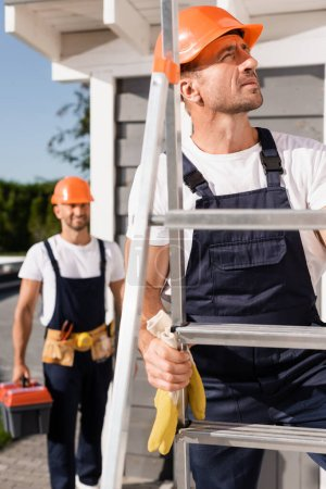 Photo for Selective focus of builder in hardhat standing on ladder near colleague and building - Royalty Free Image