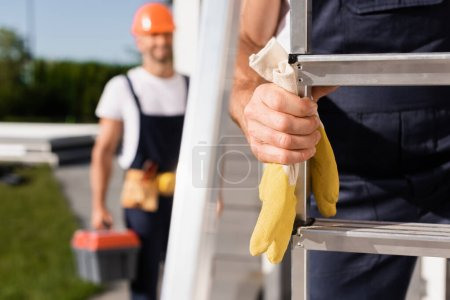 Selective focus of handyman holding gloves near ladder and colleague on urban street