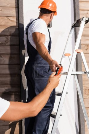 Photo pour Concentration sélective du constructeur donnant des pinces à un collègue sur l'échelle près de la maison - image libre de droit