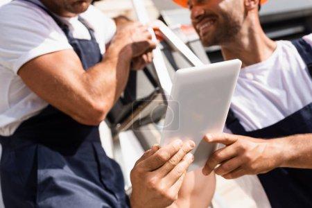 Photo pour Vue recadrée de bricoleurs utilisant une tablette numérique près de l'échelle à l'extérieur - image libre de droit