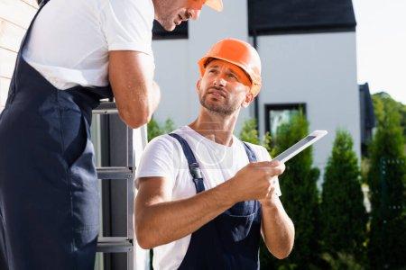 Photo pour Concentration sélective du constructeur en salopette tenant tablette numérique près de collègue sur l'échelle et la maison - image libre de droit