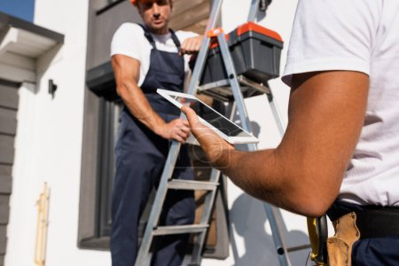 Photo pour Selective focus of manual worker holding digital tablet beside colleague on ladder and building outdoors - image libre de droit