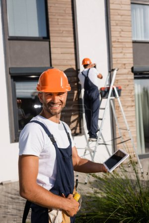 Photo pour Selective focus of builder holding digital tablet while colleague working on ladder near building - image libre de droit