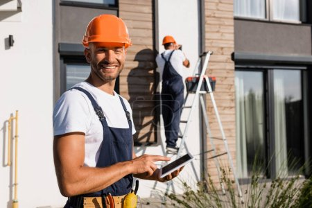 Photo for Selective focus of builder pointing with finger at digital tablet while colleague working near building at background - Royalty Free Image