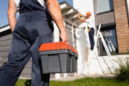 Photo pour Concentration sélective du constructeur tenant boîte à outils tout en collègue travaillant près de la maison à l'arrière-plan - image libre de droit