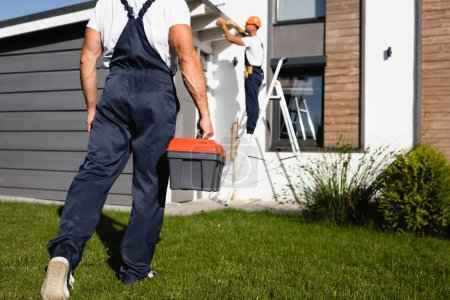 Photo for Selective focus of workman with toolbox walking on lawn while colleague working near building - Royalty Free Image