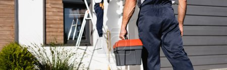 Photo pour Panoramic crop of builder in uniform holding toolbox near house outdoors - image libre de droit