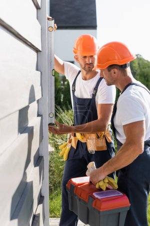 Photo for Selective focus of workmen with tools using spirit level while working with facade of building - Royalty Free Image