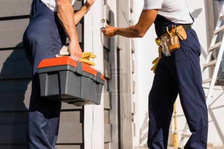Photo pour Cropped view of builder holding toolbox and gloves near colleague with spirit level and building - image libre de droit