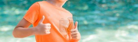 Foto de Recortado vista de niño en naranja camiseta mostrando pulgares hacia arriba, encabezado del sitio web - Imagen libre de derechos