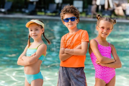 Photo for Boy in sunglasses and girls in swimsuits posing with crossed arms near pool - Royalty Free Image