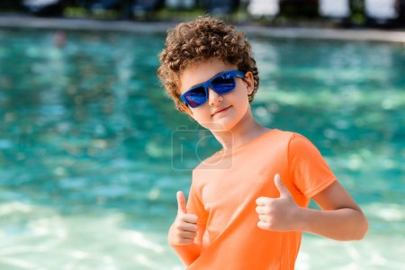 curly boy in blue sunglasses and orange t-shirt showing thumbs up near pool